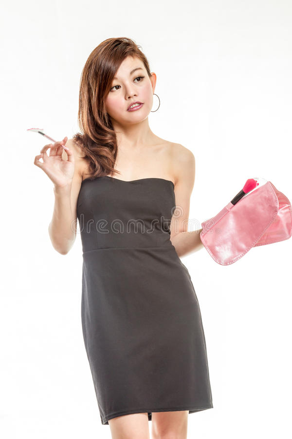 Femme asiatique attirante appliquant le maquillage photo stock