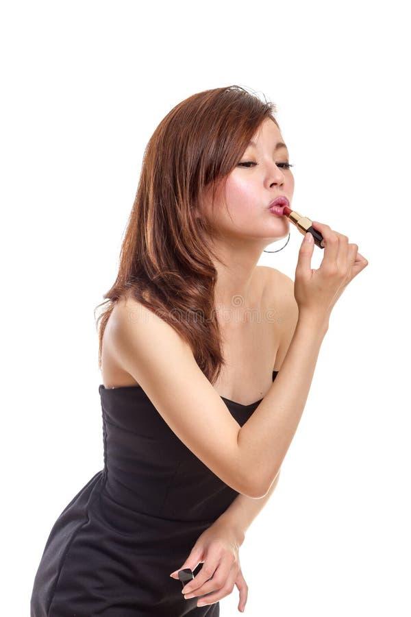 Femme asiatique attirante appliquant le rouge à lèvres image libre de droits