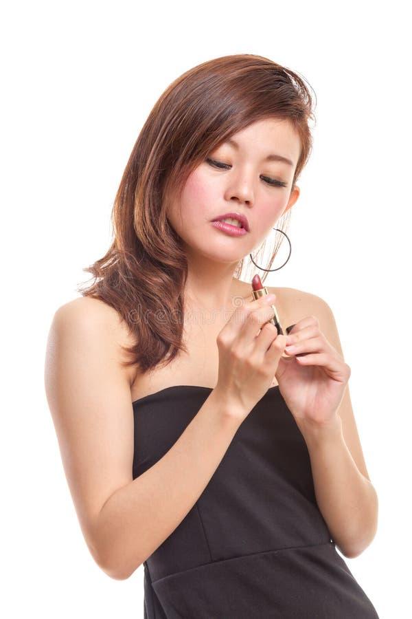 Femme asiatique attirante appliquant le rouge à lèvres images stock