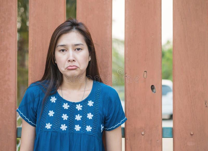 Femme asiatique avec émotion triste de visage sur le fond en bois brouillé de barrière photos stock