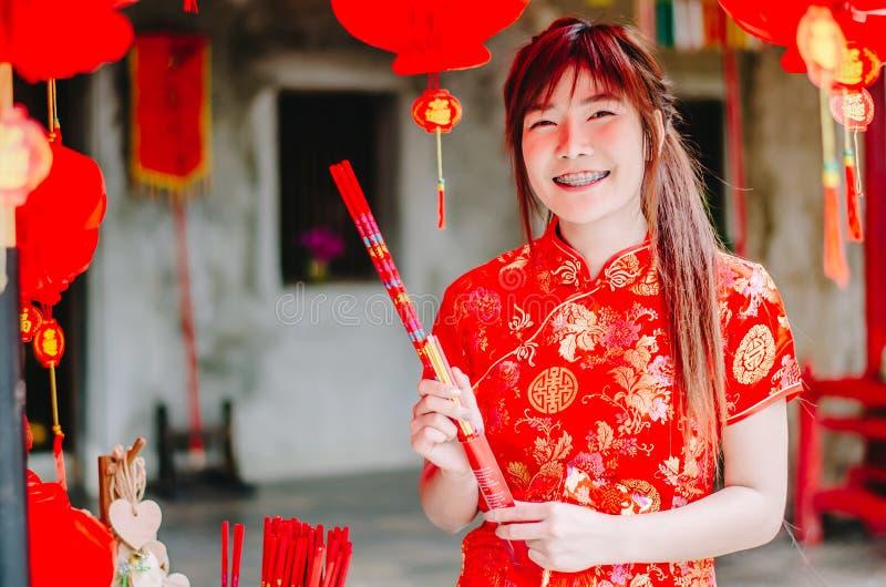 Femme asiatique avec du charme de portrait la belle portent le cheongsam pour s'habiller pour choisir d'acheter l'encens, par nou photo stock