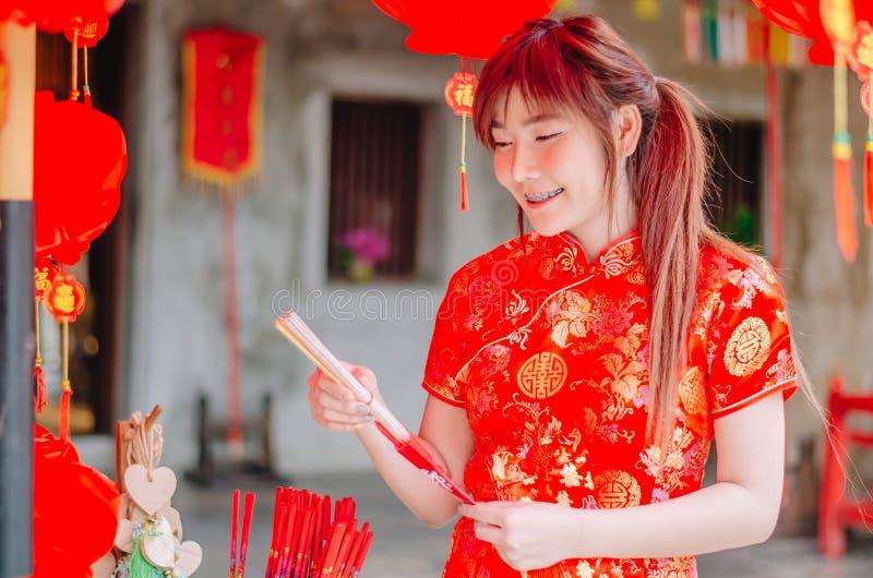 Femme asiatique avec du charme de portrait la belle portent le cheongsam pour s'habiller pour choisir d'acheter l'encens, par nou photos stock