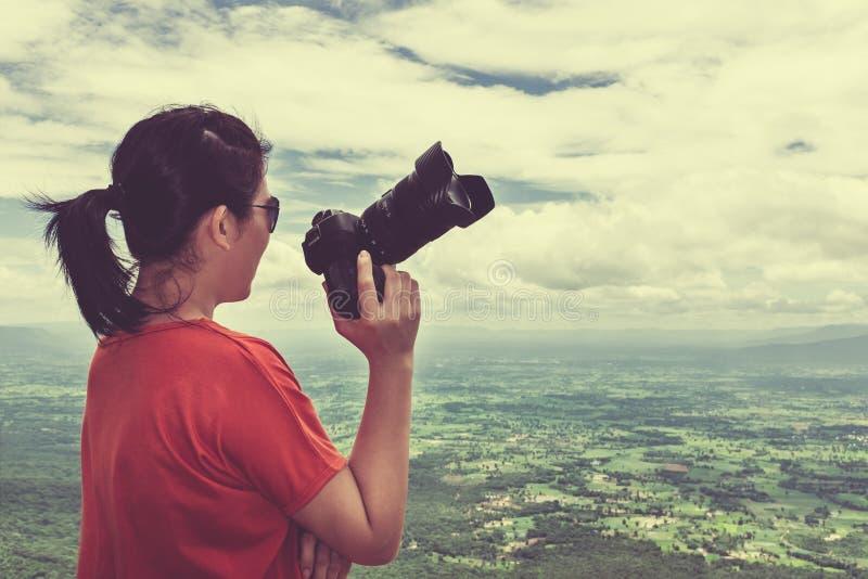 Femme asiatique avec l'appareil photo numérique, extérieur à la journée sur le summe photos stock