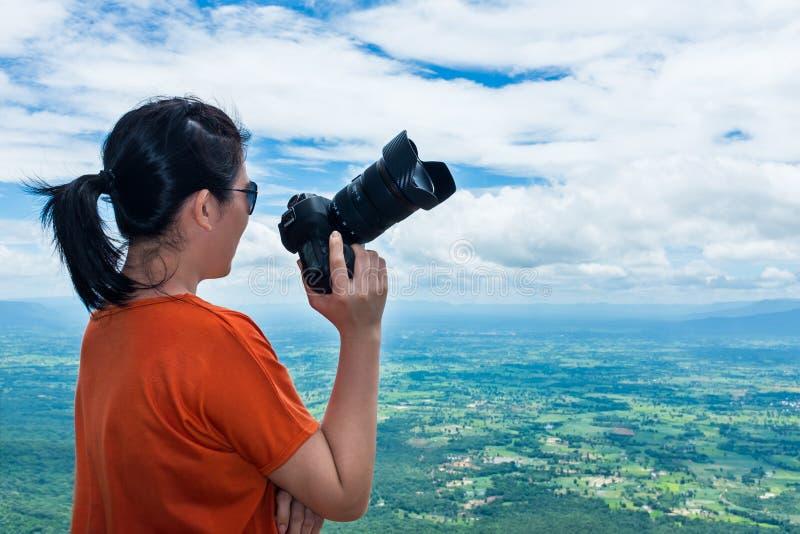 Femme asiatique avec l'appareil photo numérique, extérieur à la journée sur le summe images stock