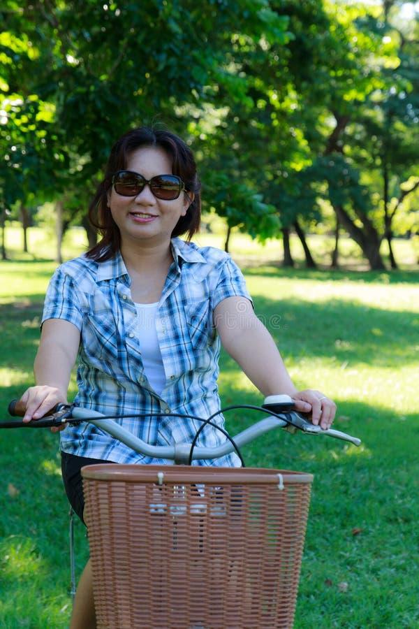 Femme asiatique avec la bicyclette photos stock