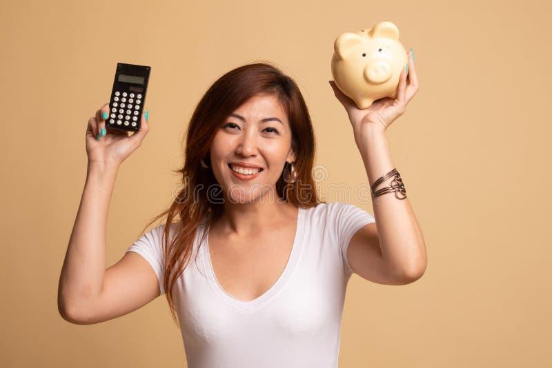 Femme asiatique avec la calculatrice et la tirelire image stock