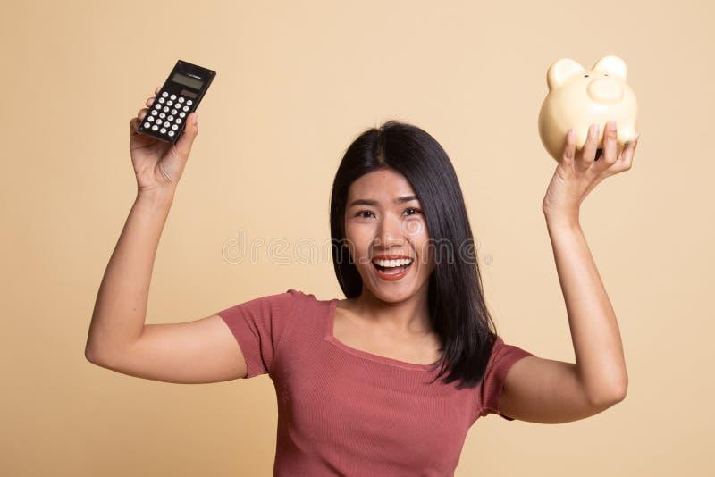 Femme asiatique avec la calculatrice et la tirelire photos stock