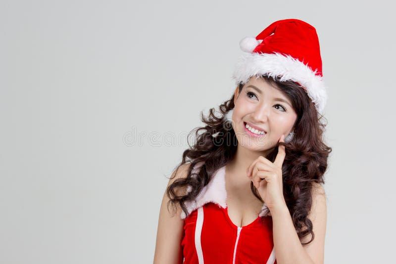 Femme asiatique avec la pensée de robe de Santa images stock