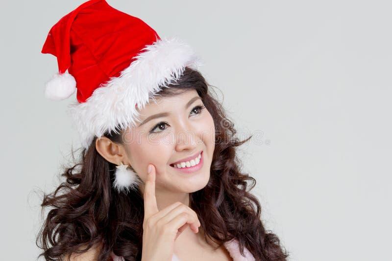 Femme asiatique avec la pensée de robe de Santa image stock