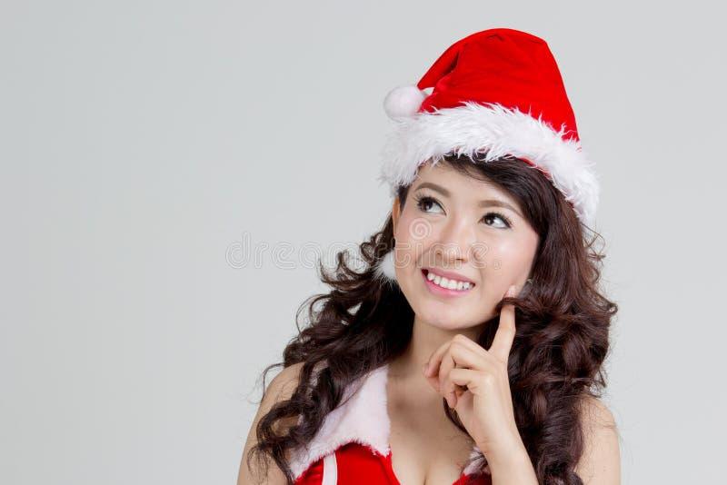 Femme asiatique avec la pensée de robe de Santa photo libre de droits