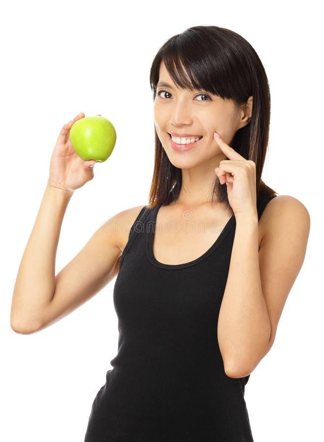 Femme Asiatique Avec La Pomme Verte Et Le Sourire Toothy Photo stock