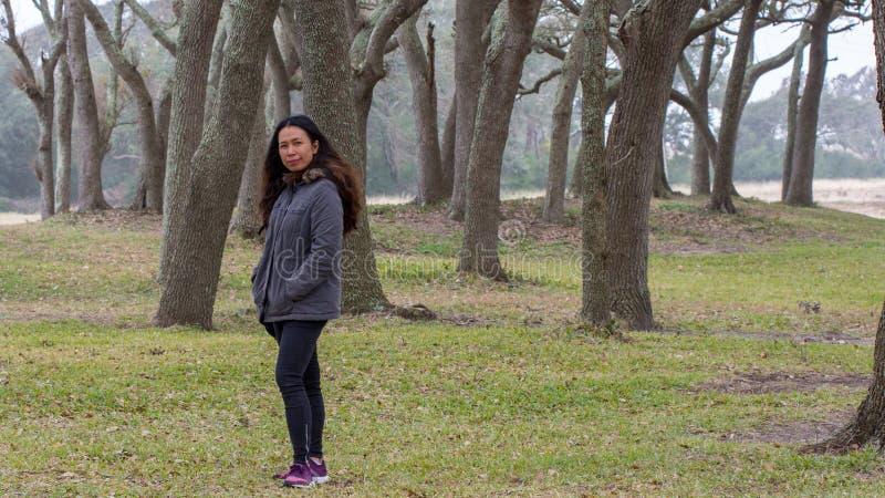 Femme asiatique avec la position de parka devant des arbres photos stock