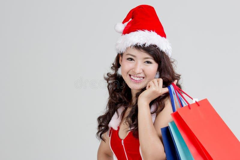 Femme asiatique avec la robe de Santa tenant les paniers colorés image stock