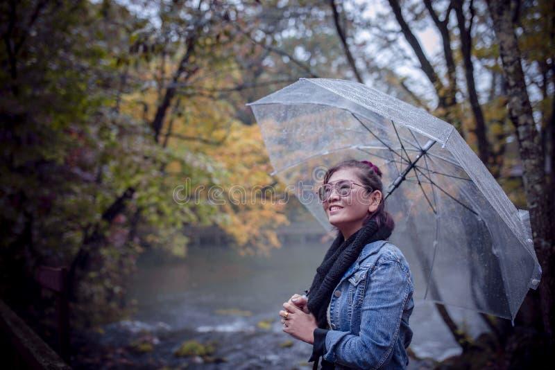 Femme asiatique avec le sourire toothy de parapluie de pluie avec le sta de bonheur image libre de droits
