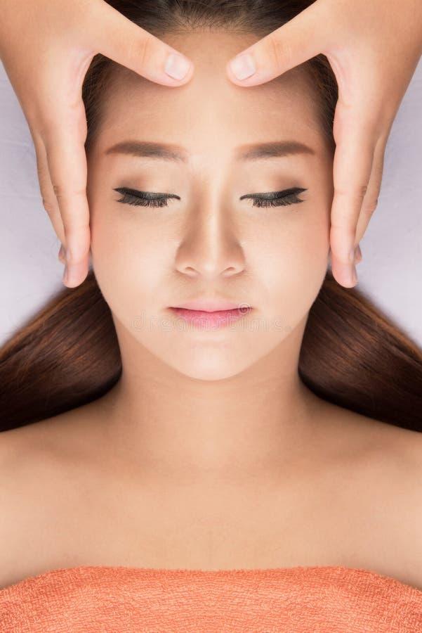 Femme asiatique ayant le massage de station thermale de la tête images stock