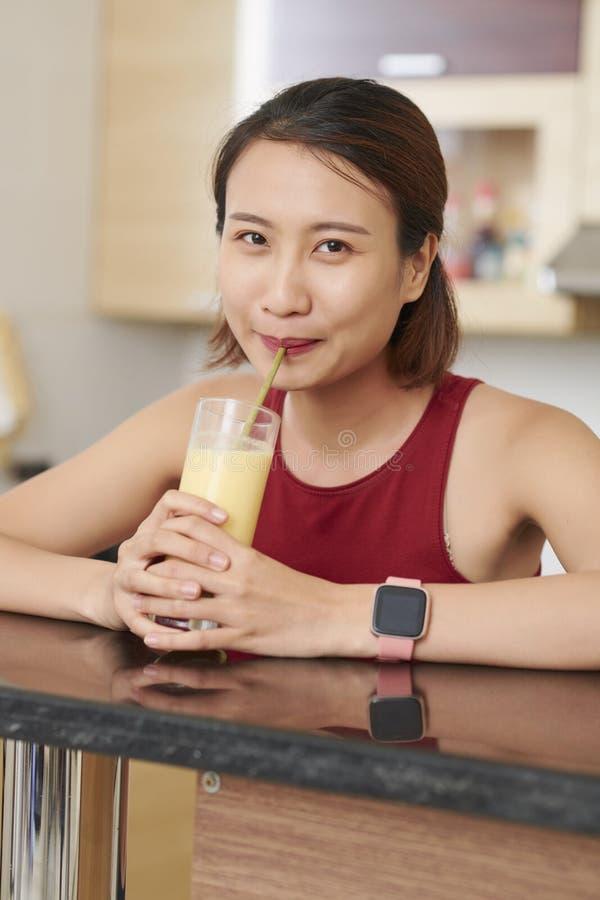 Femme asiatique buvant la macédoine de fruits savoureuse image stock