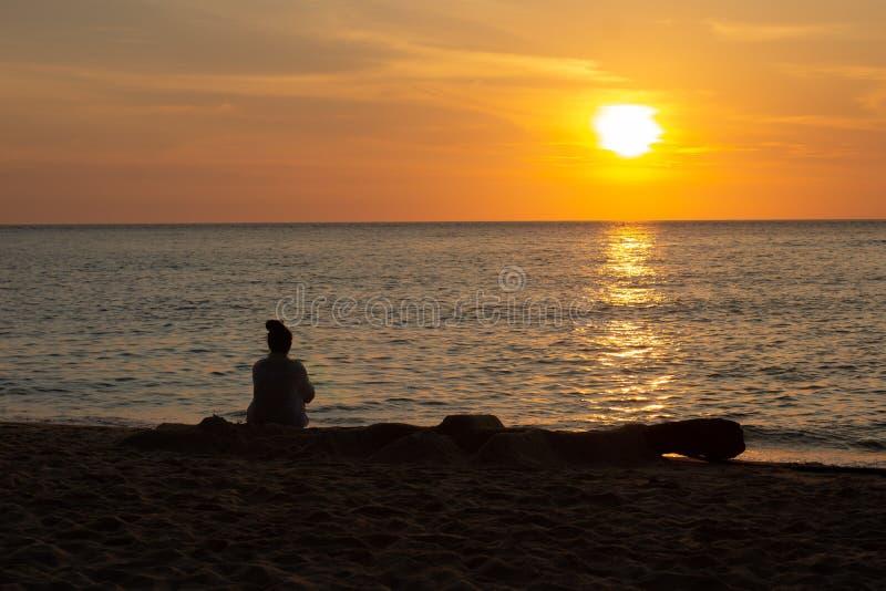 Femme asiatique cambodgienne observant le coucher du soleil et le bateau par l'océan photo stock