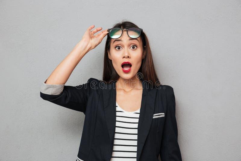 Femme asiatique choquée d'affaires tenant des lunettes et regardant l'appareil-photo photos stock