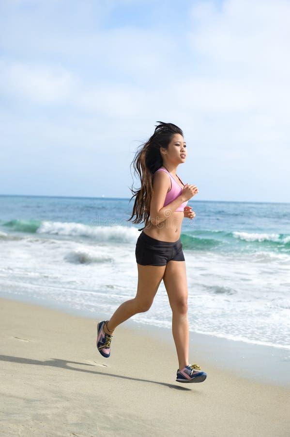 Femme asiatique courant à la plage photographie stock