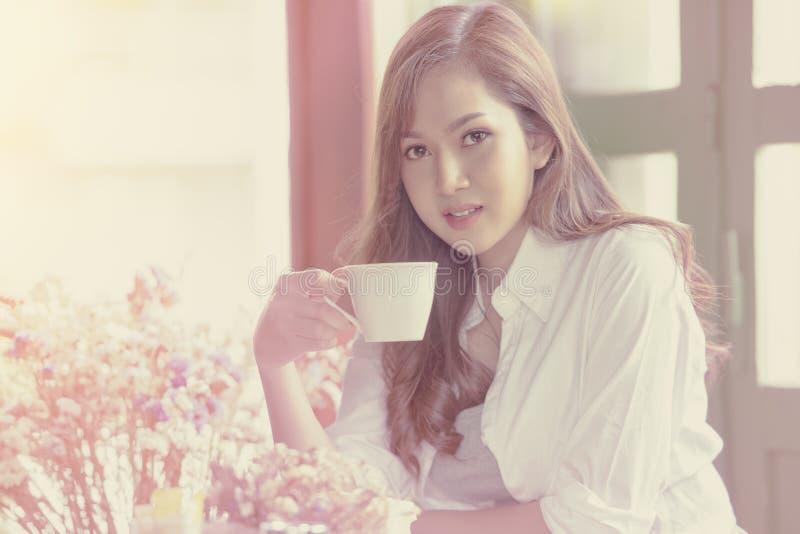 Femme asiatique détendant avec du café dans le salon image stock