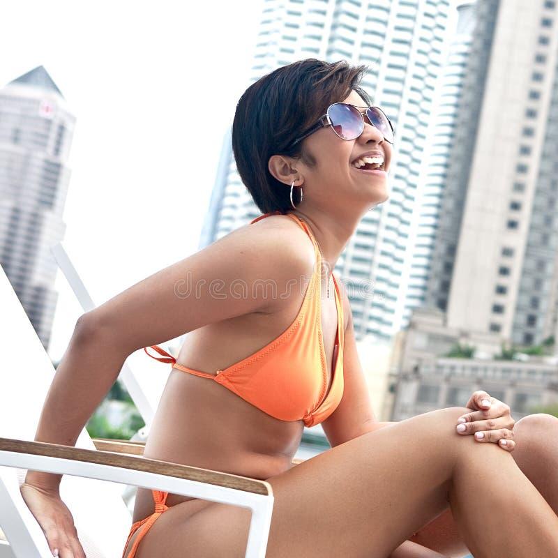Femme asiatique détendant par le regroupement photographie stock libre de droits