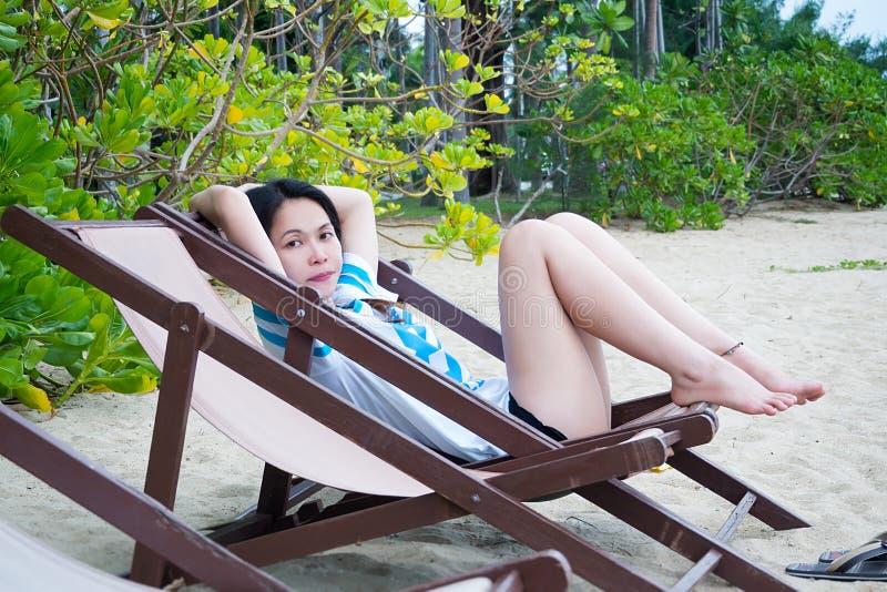 Femme asiatique détendant sur la chaise de plage dans des vacances d'été sur la plage tropicale photographie stock libre de droits