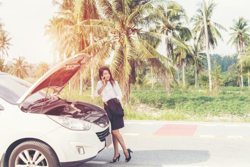 Femme asiatique d'affaires avec une voiture cassée réclamant l'aide images libres de droits