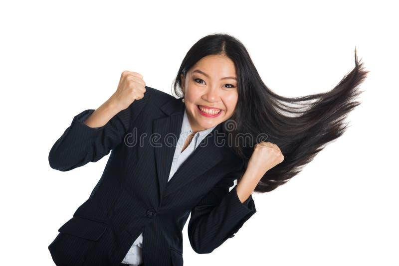 Femme asiatique d'affaires célébrant le succès avec l'oscillation de cheveux photo stock