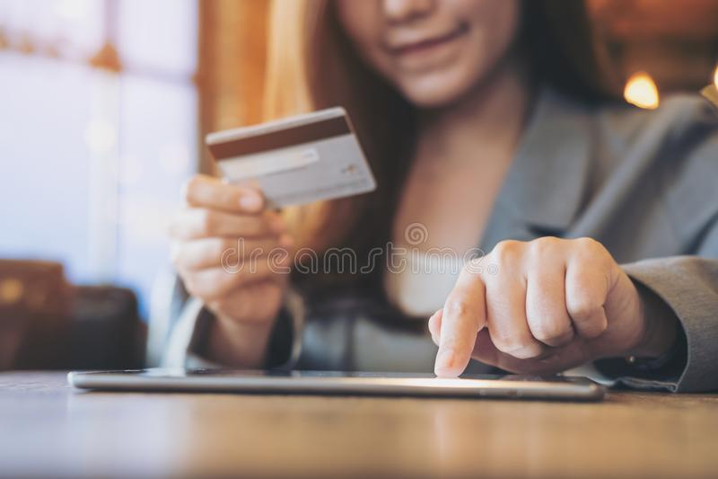Femme asiatique d'affaires tenant la carte de crédit tout en à l'aide du comprimé photos libres de droits