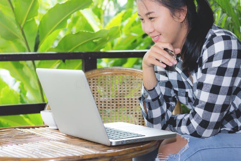 Femme asiatique d'affaires travaillant avec l'ordinateur portable et regardant dans le moniteur photo libre de droits
