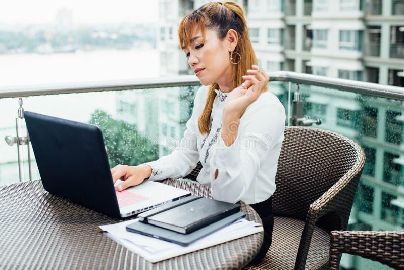Femme asiatique d'affaires travaillant dans le bureau sur la plate-forme photos stock