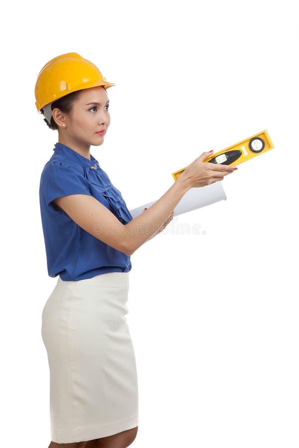 Femme asiatique d'ingénieur avec les modèles et le niveau photo stock