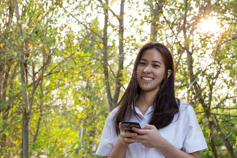 Femme asiatique d'université de portrait à l'aide du téléphone portable avec le beau sourire photo libre de droits