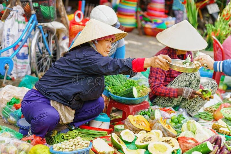 Femme asiatique dans des chapeaux vietnamiens traditionnels vendant le vegetab frais image libre de droits