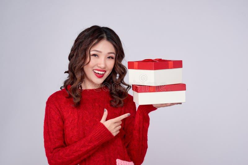 Femme asiatique dans des vêtements chauds rouges avec des cadeaux Vacances nouvelle année et Noël image libre de droits