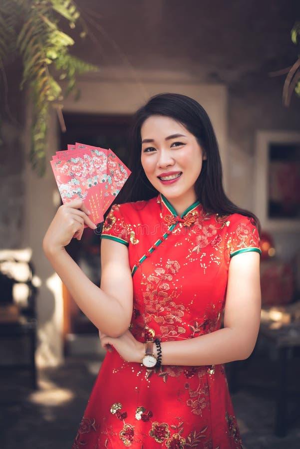 Femme asiatique dans la robe rouge traditionnelle de Cheongsam tenant l'enveloppe rouge pour donner Ang Pao pendant la nouvelle a image libre de droits