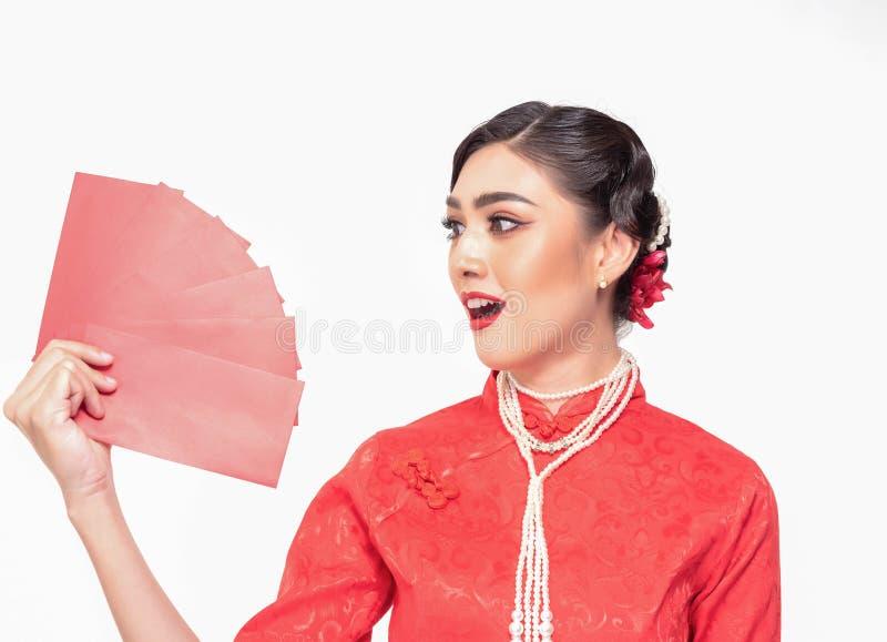 Femme asiatique dans la robe traditionnelle rouge chinoise, belle pile rouge de participation de rouge à lèvres de paquet rouge a photos libres de droits