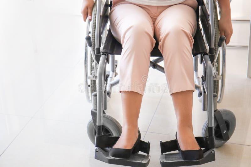 Femme asiatique dans le fauteuil roulant dans le bureau photographie stock libre de droits