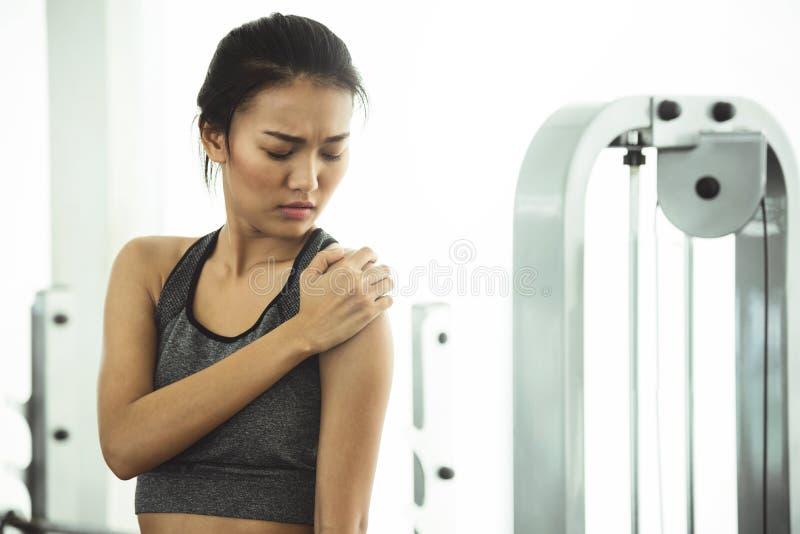 Femme asiatique dans les vêtements de sport ayant la douleur d'épaule photo libre de droits