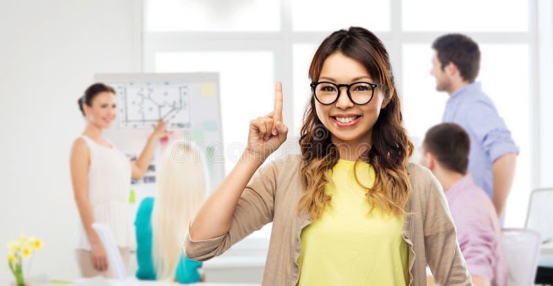 Femme asiatique dans les verres ou l'?tudiant avec le doigt  image stock