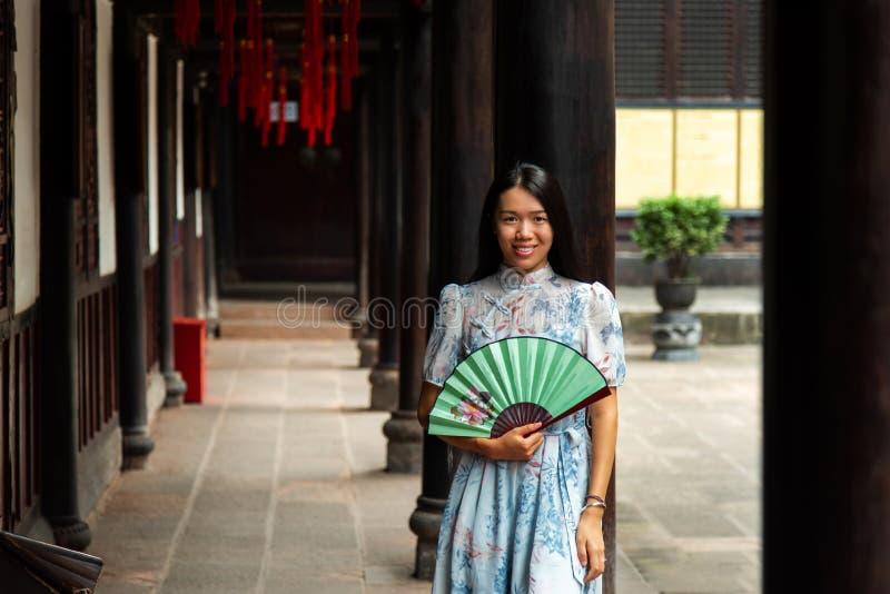Femme asiatique dans un temple tenant une fan de main photos stock