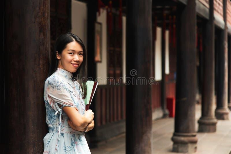 Femme asiatique dans un temple tenant une fan de main images libres de droits