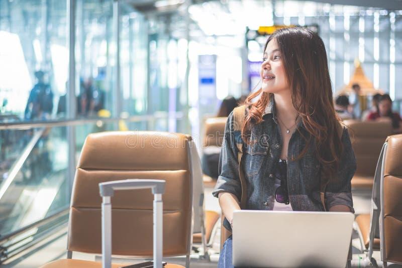 Femme asiatique de beauté à l'aide de l'ordinateur portable et regardant extérieur l'aéroport image libre de droits