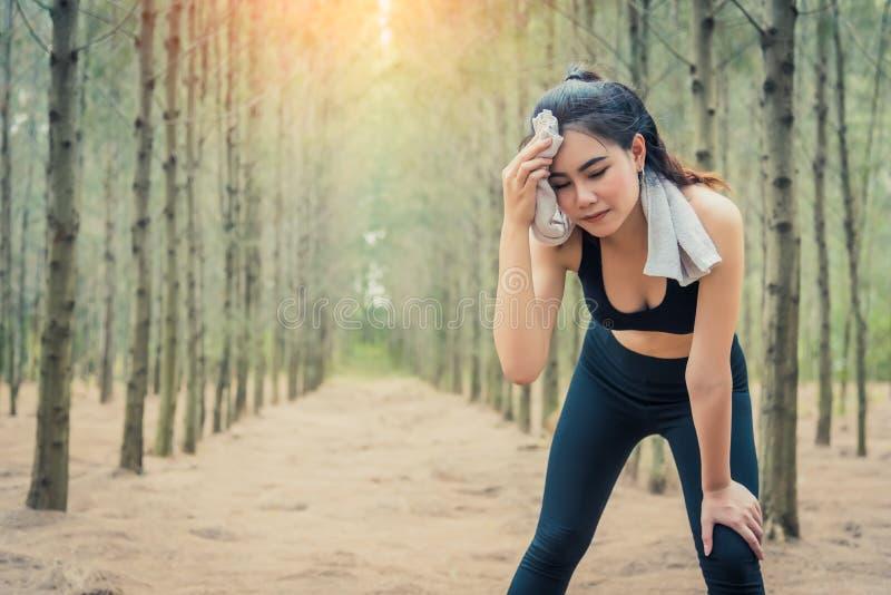 Femme asiatique de beauté essuyant la sueur dans des éléments de serviette et de sueur de forêt Sport et concept sain Concept pul photos libres de droits