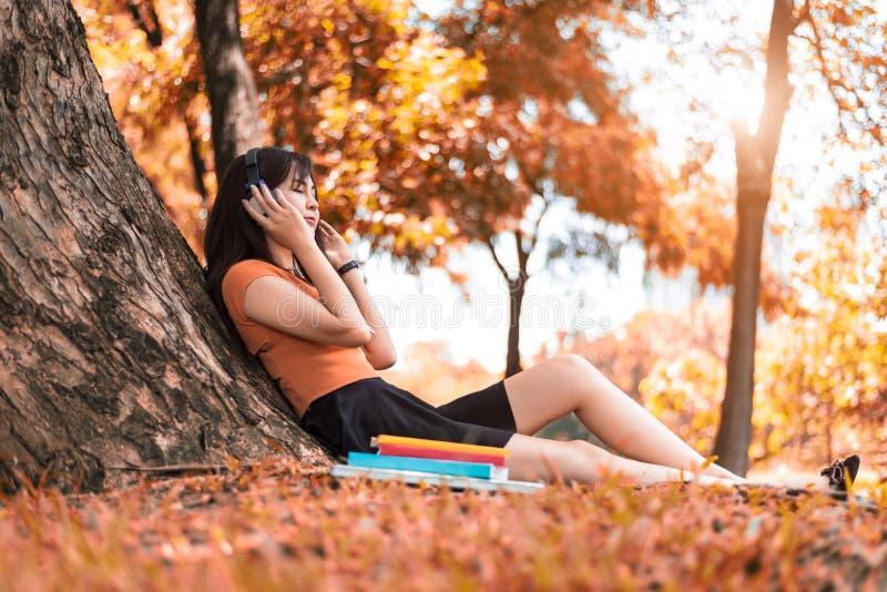 Femme asiatique de beaut? ?couter la musique en parc Modes de vie de personnes et concept de divertissement Concept de relaxation photographie stock libre de droits