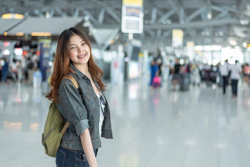 Femme asiatique de beaut? heureuse voyageant et tenant la valise dans le terminal d'a?roport avec le fond de passag?res de person photos libres de droits