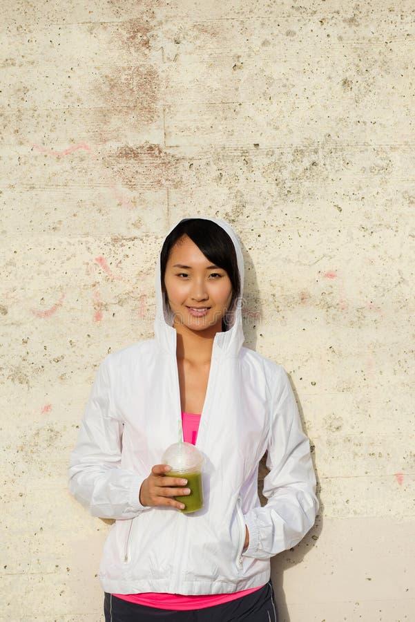 Femme asiatique de forme physique prenant un repos pour le smoothie potable de detox photos stock