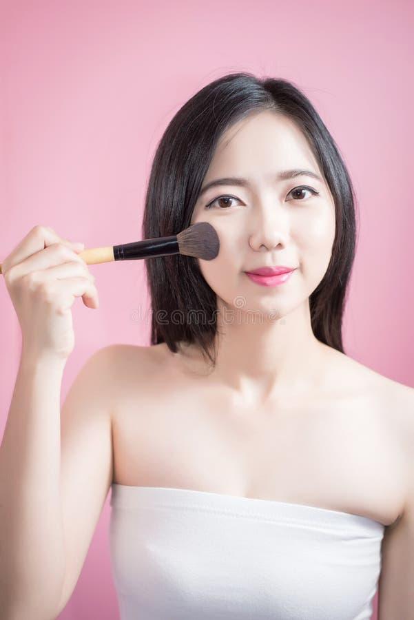 Femme asiatique de longs cheveux jeune belle appliquant la brosse cosmétique de poudre sur le visage lisse d'isolement au-dessus  image libre de droits