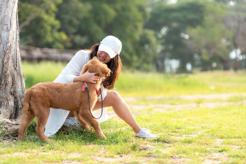 Femme asiatique de mode de vie jouant avec le chien d'amitié de golden retriever si heureux et détendre près de la route photos stock