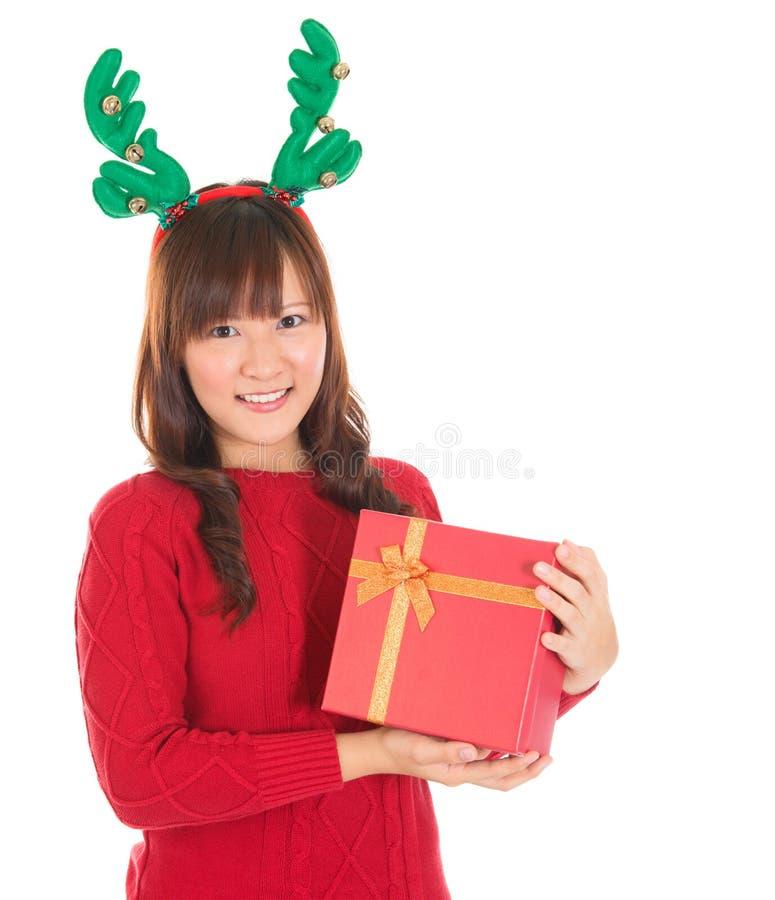 Femme asiatique de Noël tenant les klaxons de port de renne de cadeau. image stock